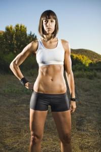 Portrait of a female runner standing in an open field.