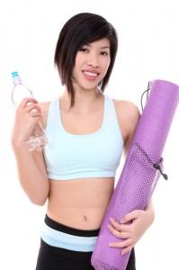 fit women with yoga mat and water
